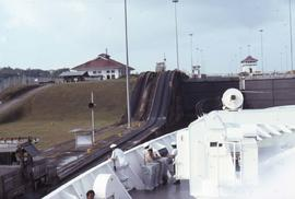 White boat with people sitting along the side going through the Panama Canal