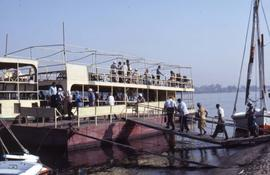 Unidentified people walking up a gangplank of a river cruise boat