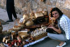 Phyliss Snider crouching next to items on the ground that are for sale