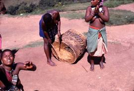 Unidentified South African  women in traditional ethnic dress beating a traditional drum