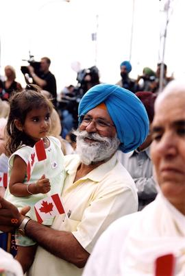 [A man in a blue turban holding a young girl with a Canadian flag]