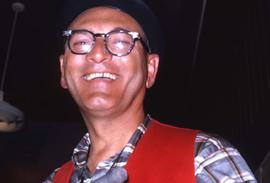 Unknown man wearing a red vest smiling at the camera