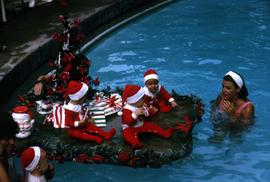 Young children in Santa costumes sitting by a pool next to a Christmas tree