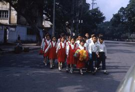 Group of children in uniform crossing the street