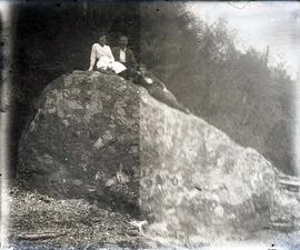 [Three unidentified people sitting on a rock]