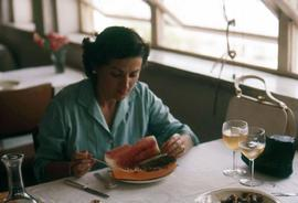 Phyliss Snider sitting at a table, possibly in a restaurant, eating fruit