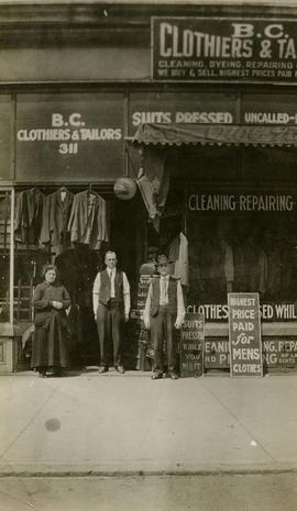[Mrs. Ann Snider and two unknown men posing in front of one of Mrs. Snider's tailor shops]