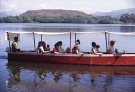 People sitting in a red boat with a white awning in a body of water with mountains in the background