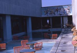 Several tables with orange chairs in a pool in the centre of a building with a wall in the backgr...