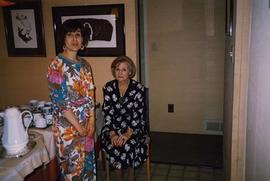 [Phyliss Snider sitting on a chair and an unknown woman standing next to her]