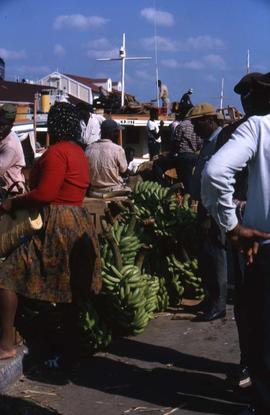 Crowd of people with bananas in the centre and a boat in the background