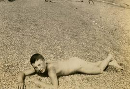 [Young Irving Snider laying naked on a beach]