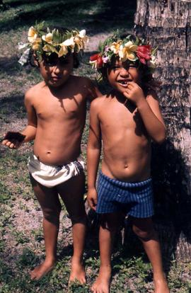 Two children standing next to a tree wearing hats made out of flowers