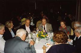 [Group of unknown people sitting around a table at an unknown event]