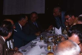 Group of unknown men sitting around a table having a discussion