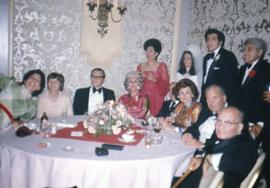 Group of people including Dr. Irving and Phyliss Snider and an unknown bride sitting and standing around a table