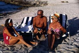 Phyliss Snider and an unknown man and woman sitting on beach chairs