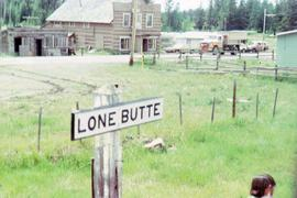 Sign for Lone Butte with a log house in the background