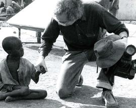 [Bernie Simpson kneeling down and holding an Ethiopian child's hand]