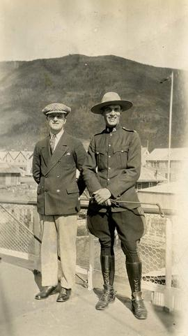 [Two unknown men, one of whom is wearing a Mountie uniform, posing for the camera]