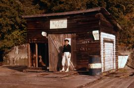 "Phyliss Snider standing in front of a small shack that has a sign on it that says: ""Scow Bay..."