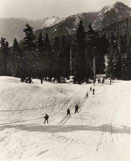 Skiers using a tow rope on the Grouse Mountain ski hill
