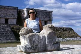 Phyliss Snider posing beside the twin-jaguar alter in front of the Palace of the Governor