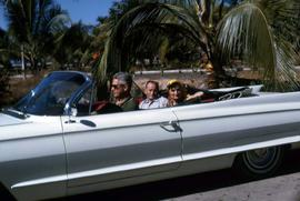 Harry Nemetz and Phyliss Snider riding in a white convertible with an unknown man driving