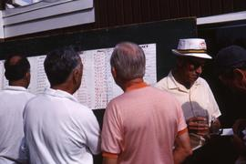 Five unknown men looking at a white poster with several categories on it