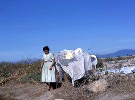 Woman with laundry laid out on a leafless bush