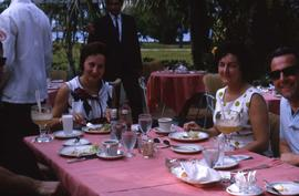 Two unknown men and two unknown women sitting at a table eating
