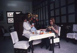 Woman sitting at a restaurant table while being served by another woman