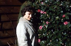 Phyliss Snider next to a rose bush