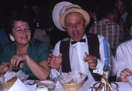 Unknown man and woman sitting at a table eating