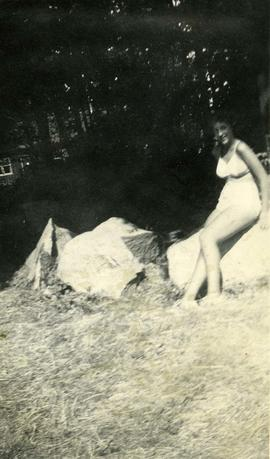 Unidentified girl sitting on a rock