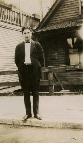 [Young Irving Snider posing for the camera with a house behind him]