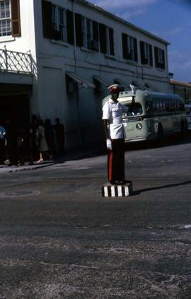 Traffic policeman in uniform standing on a platform in the centre of an intersection