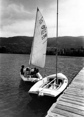 Children in sailboat next to dock at Camp Hatikvah