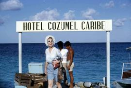 "Unknown woman posing for the camera with a sign over her head that reads: ""Hotel Cozumel Car..."