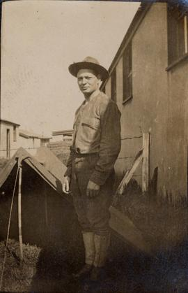 Unidentified man in front of tent
