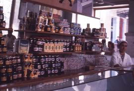 Cans and jars on display behind store counter