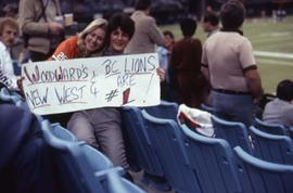 "Two unknown woman sitting in the stands of BC Place holding a sign that reads: ""Woodward's N..."