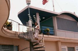 Phyliss Snider standing on the spiraling staircase of a house