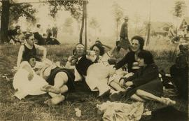 Unidentified group of people sitting on grass