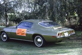 "Green car parked with an orange sign on the side that says: ""Dueck Hole in One Prize"""