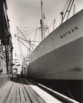 "Vessel ""Bataan"" at dock, unloading cars"