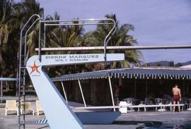 "Pool diving board with the words ""Pierre Marques, Hotel V Bungalows"" painted on the side"