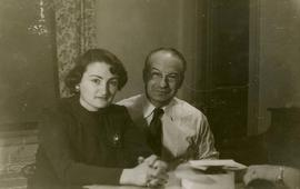 [Dr. Irving and Phyliss Snider sitting at a table and posing for the camera in their home in Whyt...