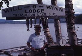 Dr. Irving Snider posing in front of  a sign with fish hanging from it and a fish scale