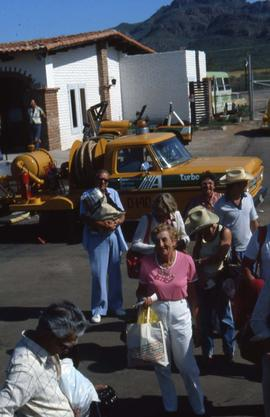 Group of unknown people standing in front of a yellow truck